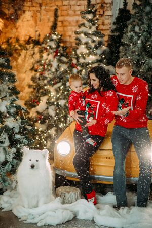 Happy family with little son stands next to white samoyed dog against background of Christmas tree, retro car and snowfall. Zdjęcie Seryjne - 136099091
