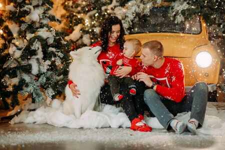 Happy family with little son sits next to white samoyed dog against background of Christmas tree, retro car and snowfall. Zdjęcie Seryjne - 136099108