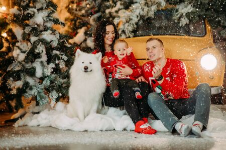 Happy family with little son sits next to white samoyed dog against background of Christmas tree, retro car and snowfall.