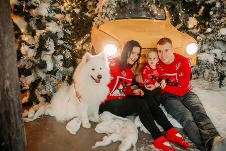 Happy family with little son sits next to white samoyed dog against background of Christmas tree and retro car. Zdjęcie Seryjne - 136099103