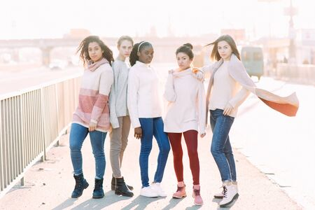 Multiracial group of friends from five young women walks on city street. The concept of friendship and unity between different human races.