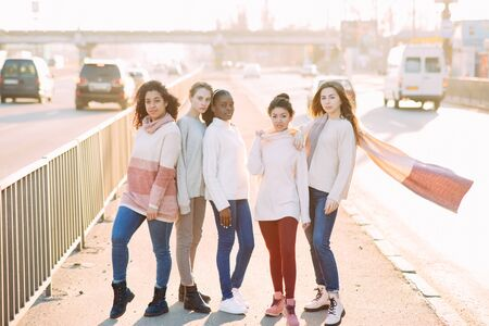Multiracial group of friends from five young women walks on city street. The concept of friendship and unity between different human races. Zdjęcie Seryjne - 137551661