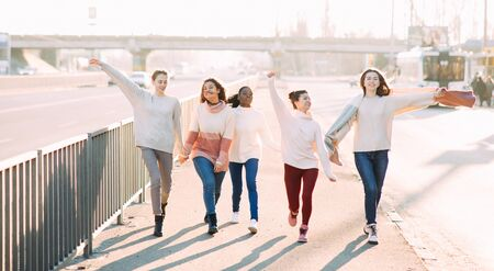 Multiracial group of friends from five young women walks and has a fun on city street. The concept of friendship and unity between different human races. Zdjęcie Seryjne