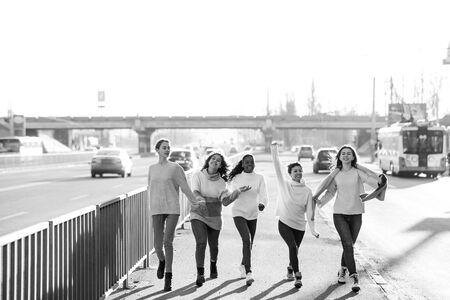Multiracial group of friends from five young women walks and has a fun on city street. The concept of friendship and unity between different human races. Black and white image.