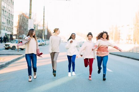 Multiracial group of friends from five young women runs and has a fun on city street. The concept of friendship and unity between different human races.