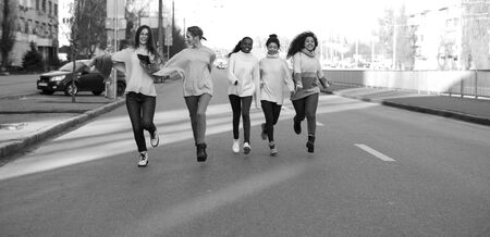 Multiracial group of friends from five young women runs and has a fun on city street. The concept of friendship and unity between different human races. Black and white image.