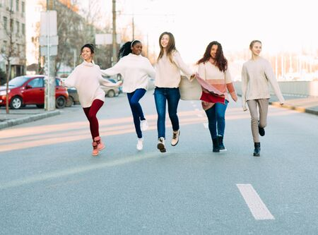 Multiracial group of friends from five young women runs and has a fun on city street. The concept of friendship and unity between different human races. Zdjęcie Seryjne - 137398509