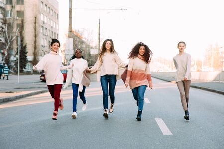 Multiracial group of friends from five young women runs and has a fun on city street. The concept of friendship and unity between different human races. Zdjęcie Seryjne - 137399519