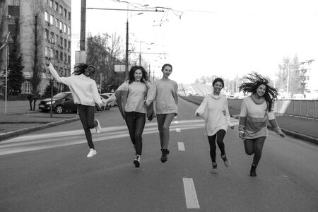 Multiracial group of friends from five young women runs and has a fun on city street. The concept of friendship and unity between different human races. Black and white image. Zdjęcie Seryjne - 137304577