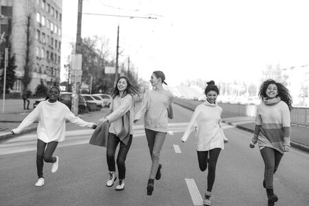 Multiracial group of friends from five young women runs and has a fun on city street. The concept of friendship and unity between different human races. Black and white image. Zdjęcie Seryjne - 137398511