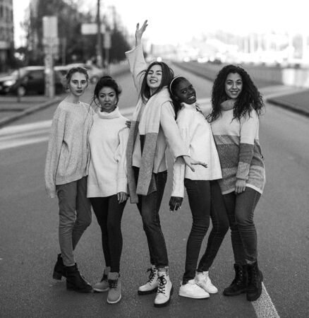 Multiracial group of friends from five young women stands on city street. The concept of friendship and unity between different human races. Black and white image.