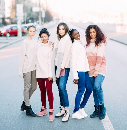 Multiracial group of friends from five young women stands on city street. The concept of friendship and unity between different human races.