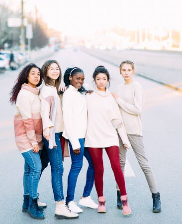 Multiracial group of friends from five young women stands on city street. The concept of friendship and unity between different human races. Zdjęcie Seryjne - 137551699