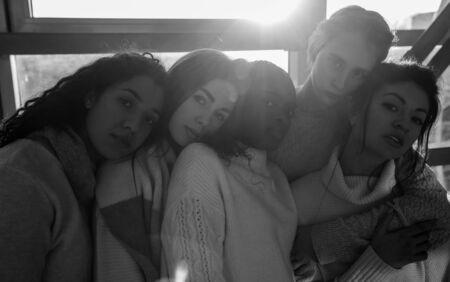 El retrato del grupo multirracial de cinco mujeres. El concepto de amistad y unidad entre diferentes razas humanas. Imagen en blanco y negro.