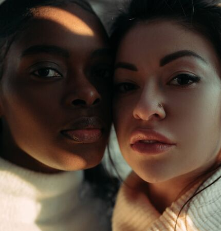 The portrait of young african and asian women with sunlit areas. The concept of friendship and unity between different human races. Zdjęcie Seryjne - 137399256