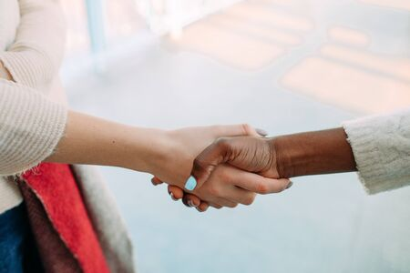 Handshake of two women of different races closeup. The concept of friendship and unity between different human races. Zdjęcie Seryjne