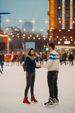 Young couple skates at the rink and holds hands on the background of evening city lights.
