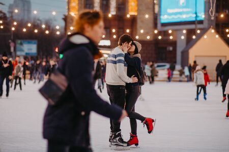 Young couple skates at the rink and kisses on the background of evening city lights.