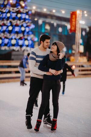 Young couple skates at the rink on the background of Christmac tree and decorations.