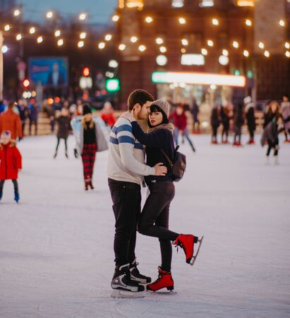 Young couple skates at the rink and embraces on the background of evening city lights.