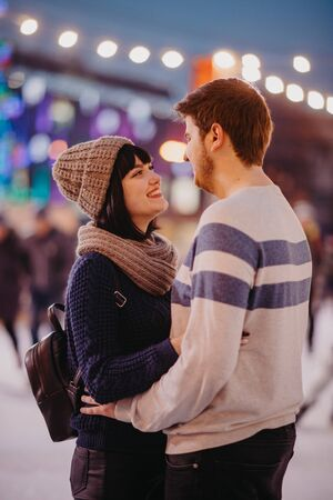 Young couple stands and embraces on the background of evening city lights.