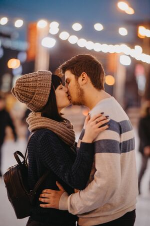 Young couple stands and kisses on the background of evening city lights.