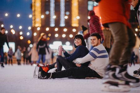 Young couple sits on the ice rink and drinks hot tea from a flask.