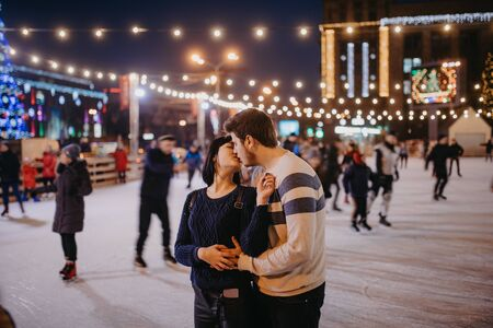 Young couple skates at the rink and kisses on the background of of evening city lights.