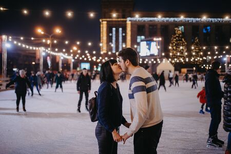 Young couple skates at the rink, kisses and holds hands on the background of Christmac decorations.