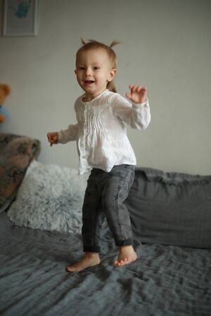 Toddler girl has a fun, frolics and jumps on the bed.