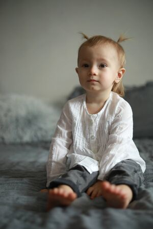 Toddler girl in white shirt sits on the bed. Zdjęcie Seryjne