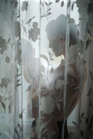 Mother with baby on her arms stands next to window. View through transparent curtain.