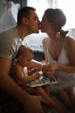 Baby girl sits and plays next to kissing parents. Zdjęcie Seryjne