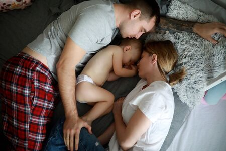 Family with baby sleeps together on the bed. Top view.