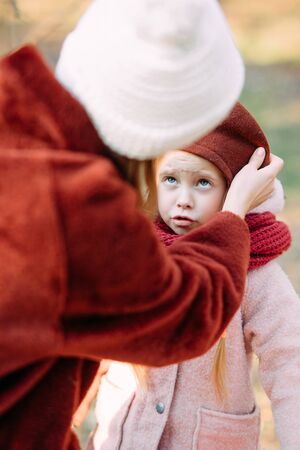 Mother puts on beret on head of her daughter, the girl is unhappy with this. Zdjęcie Seryjne