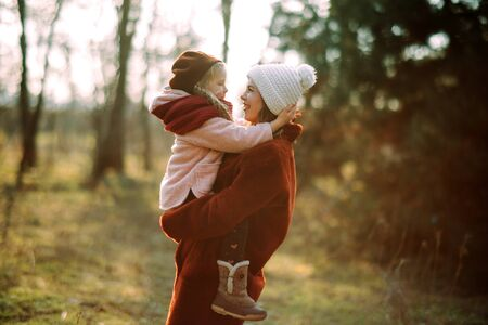 Mother and daughter play, have fun and laugh cheerful while walking in the forest.
