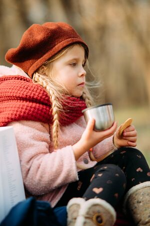 Girl drinks hot tea with a thermos and eats cookies while walking in the forest.