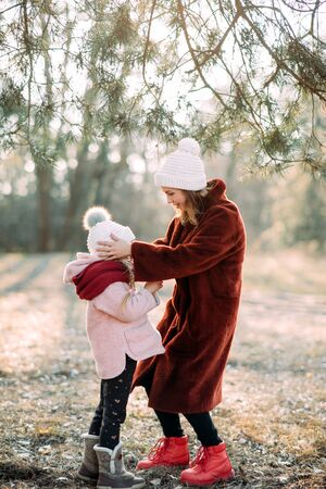 Mother and daughter play and have fun while walking in the pine forest. Zdjęcie Seryjne