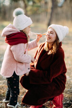 Mother and daughter play and have fun while walking in the forest. Zdjęcie Seryjne