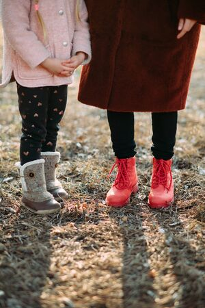 Child and woman feet are in boots on the background of pine needles in the forest.