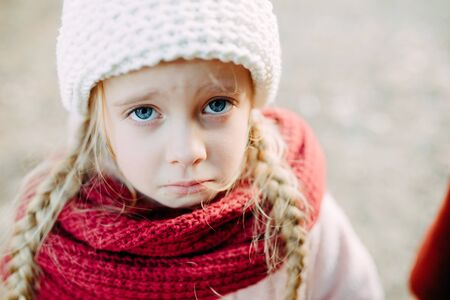 Portrait of a child girl with pigtails in a hat and scarf with an resentful expression Zdjęcie Seryjne