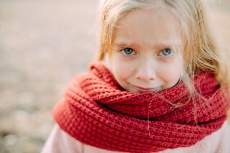 Portrait of a child girl in a scarf with resentful expression and tears on her face.