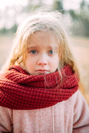 Portrait of a child girl in a scarf with resentful expression and tears in her eyes. Zdjęcie Seryjne