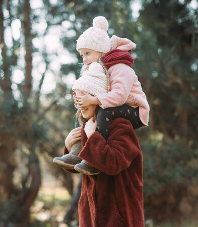 Mother and daughter play, have fun and smile cheerful while walking in the forest.