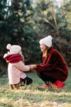 Mother and daughter play, hold hands and laugh cheerful during stroll in the forest. Zdjęcie Seryjne