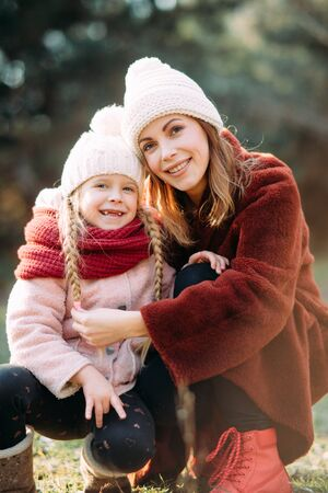 Happy mother and daughter are on stroll in the forest.