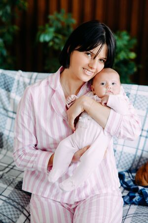 A mother in pajamas sits on a sofa and holds a baby in her arms.