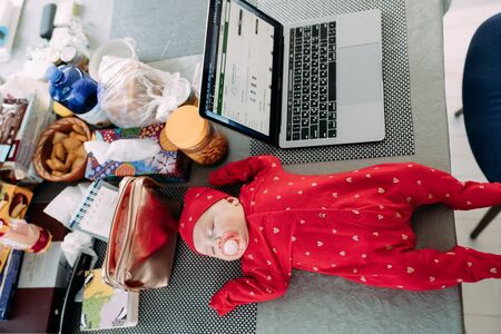 Baby sleeps on a table near an open laptop. Employment concept of women with babies. Top view.