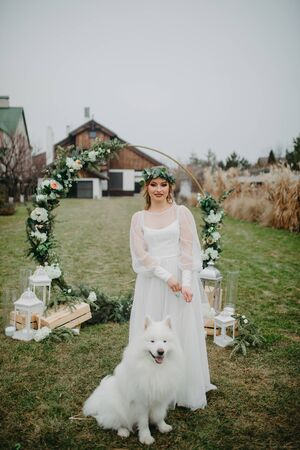 The bride stands next to a Samoyed dog and a wedding arch on the background of the lawn and the house.