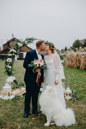 Newlyweds stand on the background of the wedding arch and kiss next to a Samoyed dog on the background of the lawn and the house. Stock Photo